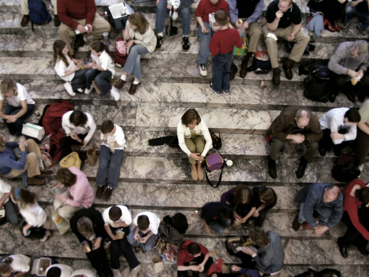 Persona seduta da sola su un gradino in mezzo a tanta agente